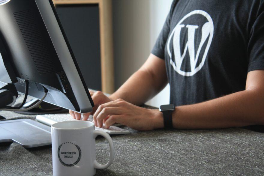 Ein Mann mit Wordpress T-Shirt sitzt vor einem Desktop-PC