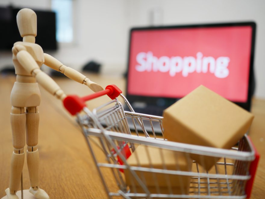 Eine Figur fährt einen mit Paketen beladenden Einkaufswagen.
